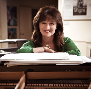 """Photograph of composer and conductor Debbie Wiseman, MBE, accompanying the historytracings blog post """"Food to Remember with Debbie Wiseman"""" exploring the poignancy of family recipes and their place within family cultural heritage. Image copyright and courtesy of Debbie Wiseman, 2016."""