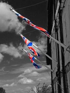 "Photograph of coloured Union Jack flags against a black and white street scene, accompanying the historytracings blog post ""Black and White in Colour - Thursday Thoughts"" from historytrace, exploring the colourful past in black and white, and colour. Image copyright: www.freeimages.com / Steve Knight."